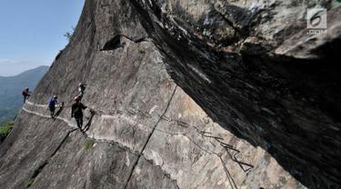 Pendaki memanjat tebing Gunung Parang via Jalur Ferrata, Desa Cihuni, Purwakarta, Jawa Barat, Sabtu (30/3). Gunung berketinggian 930 mdpl tersebut menjadi lokasi pilihan bagi pemanjat tebing lokal dan mancanegara. (merdeka.com/Iqbal Nugroho)