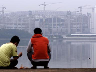 Warga menikmati waktu sore di pinggir Waduk Cincin yang berlatar pembangunan Jakarta International Stadium (JIS), Sabtu (19/6/2021). Pembangunan JIS sudah memasuki tahap pemasangan rangka atap dengan bentang mencapai 269 meter dan ditarget selesai Desember 2021. (Liputan6.com/Helmi Fithriansyah)
