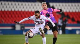 Striker OGC Nice, Alexis Claude-Maurice (kiri) berebut bola dengan gelandang Paris Saint-Germain, Leandro Paredes dalam laga lanjutan Liga Prancis 2020/21 pekan ke-25 di Parc des Princes Stadium, Paris, Sabtu (13/2/2021). Nice kalah 1-2 dari Paris Saint-Germain. (AFP/Franck Fife)