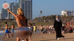 Warga Palestina dan Israel menikmati laut Mediterania selama liburan Idul Fitri, di Tel Aviv, Israel (25/5/2020).  Idul Fitri menandai akhir bulan suci Ramadhan, perayaan tiga hari yang biasanya menggembirakan telah berkurang secara signifikan karena pandemi coronavirus. (AP Photo/Oded Balilty)