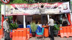 Petugas memasang spanduk di posko penjagaan Gereja Katedral, Jakarta, Sabtu (24/12). Penjagaan dilakukan untuk menjaga kondusifitas agar acara Malam Misa Natal bisa berjalan lancar. (Liputan6.com/Helmi Afandi)