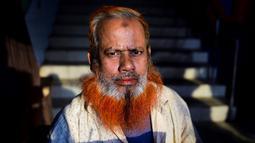 Dalam gambar yang diambil pada 24 Desember 2018, pedagang kaki lima bernama Amir Hossain dengan janggut oranye di Dhaka. Para pria tua yang ingin tetap merasa muda mewarnai janggut dengan henna, pewarna tradisional yang sudah terkenal di Bangladesh beberapa dekade lamanya. (MUNIR UZ ZAMAN / AFP)