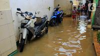 Anak-anak bermain banjir yang melanda kawasan Bidara Cina, Kecamatan Jatinegara, Jakarta Timur, Selasa (25/2/2020). Baru satu hari air surut, kawasan Bidara Cina yang bersebelahan dengan Kali Ciliwung kembali mengalami banjir. (merdeka.com/magang/ Muhammad Fayyadh)