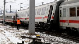 Seorang petugas regu penyelamat berdiri di lokasi tabrakan yang melibatkan dua kereta penumpang dekat stasiun di Niklasdorf, Austria, Senin (12/2).  Sebanyak 19 ambulans dan 2 kendaraan darurat di kerahkan ke lokasi kejadian. (AP/Ronald Zak)