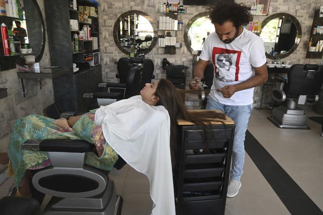 Dalam gambar pada 8 April 2021, tukang cukur Pakistan Ali Abbas menggunakan pecahan kaca untuk memotong rambut seorang pelanggan di tokonya di Lahore. Berharap membuktikan kemampuannya dalam persaingan, Ali Abbas mengandalkan berbagai alat yang tidak biasa untuk melatih keahliannya. (Arif ALI/AFP)
