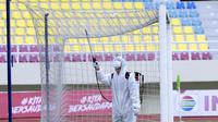 Petugas menyemprot jaring gawang dengan disinfektan sebelum pertandingan antara Persikabo 1973 melawan Arema FC pada laga Piala Menpora di Stadion Manahan, Solo, Minggu (21/3/2021). (Bola.com/M Iqbal Ichsan)