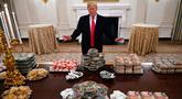 Presiden Amerika Serikat (AS) Donald Trump berpose dengan meja penuh makanan cepat saji di Gedung Putih, Washington, Senin (14 /1). Jamuan Trump ini untuk menyambut juara nasional sepak bola antarkampus, Clemson Tigers. (AP Photo/Susan Walsh)