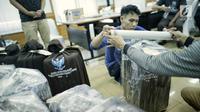 Petugas membungkus plastik paket berisi surat suara Pemilu 2019 susulan di Gedung KPU RI, Jakarta, Minggu (28/4/2019). Surat suara susulan tersebut akan dikirimkan ke Kuala Lumpur, Malaysia untuk pelaksanaan pemilihan Presiden dan Wakil Presiden. (Liputan6.com/Faizal Fanani)