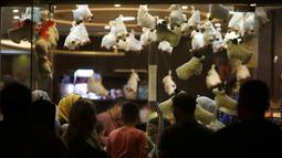 Keluarga Palestina membeli cokelat di sebuah toko yang dihiasi dengan boneka domba menjelang Hari Raya Idul Adha di kota Gaza pada Rabu (29/7/2020). (AP Photo/Hatem Moussa)
