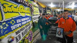 Petugas BNPB membawa jenazah Kapus Data Informasi dan Humas BNPB Sutopo Purwo Nugroho untuk diberangkatkan ke Bandara Soekarno-Hatta usai disemayamkan di rumah duka Raffles Hils, Cimanggis, Depok, Senin (7/7/2019). Sutopo diterbangkan ke Bandara Adi Soemarmo. (Liputan6.com/Herman Zakharia)