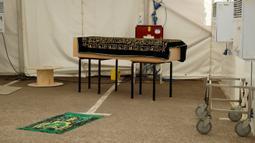Peti mati berisi jenazah korban COVID-19 diletakkan di atas meja sebelum penguburan, di halaman parkir Central Jamis Mosque Ghamkol Sharif di Birmingham, Inggris pada 24 April 2020. Masjid itu mengubah tempat parkirnya menjadi kamar mayat sementara untuk korban virus corona. (AP/Matt Dunham)