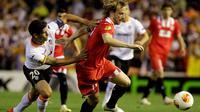 Pemain belakang Valencia, Ricardo Costa (kiri) mencoba menahan laju serangan yang dibangun gelandang Sevilla, Ivan Rakitic saat berlaga di laga kedua semifinal Liga Europa di Stadion Mestalla, Valencia (2/5/2014). (REUTERS/Heino Kalis)