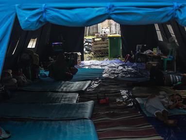 Suasana tenda pengungsian korban rumah ambles di Lodan Raya, Pademangan, Jakarta Utara, Kamis (22/11). Sebanyak delapan kepala keluarga (KK) diungsikan akibat rumah mereka ambles kena imbas pengerukan Anak Kali Ciliwung. (Liputan6.com/Faizal Fanani)