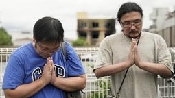 Dua pria berdoa untuk para korban kebakaran  di gedung Kyoto Animation Studio di Kyoto, Jepang (19/7/2019). Stasiun televisi NHK melapor, seorang pria yang menuangkan bensin ke sekitar gedung animasi telah ditahan. (AP Photo/Jae C. Hong)