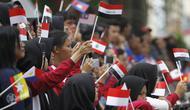 Sejumlah siswa sekolah di Solo menyambut kirab lentera  dengan membawa bendera peserta Asian Para Games 2018.(Liputan6.com/Fajar Abrori)