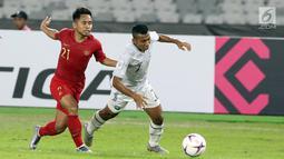 Pemain sayap Timnas Indonesia, Andik Vermansyah (kiri) berebut bola dengan pemain Timor Leste, Rufino Walter Gama pada penyisihan grup B Piala AFF 2018 di Stadion GBK, Jakarta, Selasa (13/11). Indonesia unggul 3-1. (Liputan6.com/Helmi Fithriansyah)