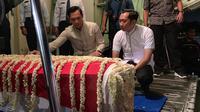 Dua putra Ani Yudhoyono, Agus Harimurti Yudhoyono dan Edhie Baskoro Yudhoyono, memegang peti jenazah dan mendampinginya saat masuk ke pesawat. (dok Partai Demokrat)