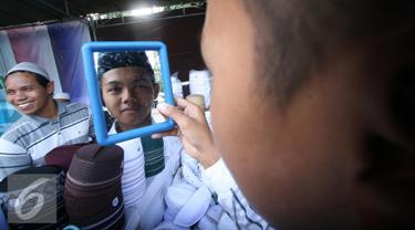 Seorang santri mencoba peci yang di tawarkan dengan kisaran harga Rp 5000 hingga Rp 55.000 di halaman masjid Ageng, Solo, Jawa Tengah, Sabtu (25/6). Omzet penjualan pedagang mengalami peningkatan selama bulan ramadan. (Liputan6.com/Boy Harjanto)