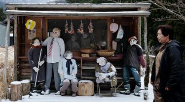 Tsukimi Ayano berjalan melewati boneka-bonekanya yang dipajang di sebuah sekolah dasar di desa kecil Nagoro, Jepang, 16 Maret 2019. Nagoro merupakan desa kecil yang ditinggali 27 penduduk dan 270 boneka. (KAZUHIRO NOGI/AFP)
