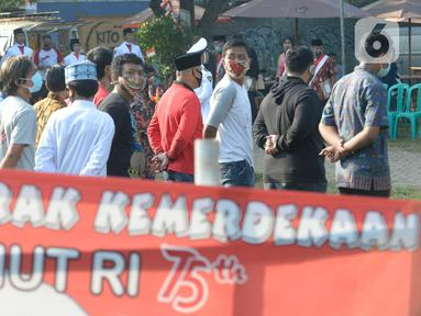 Warga Rt 06 Rw 10 mengikuti upacara HUT ke-75 Kemerdekaan RI di Kelurahan Ciater, Serpong, Tangerang Selatan, Senin (17/8/2020). Selain mengenakan baju adat, tak sedikit warga yang berpakaian seadanya untuk memperingati 17 Agustus dengan tetap menerapkan protokol Kesehatan. (merdeka.com/Dwi Narwoko)