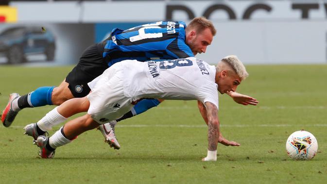 Gelandang Inter Milan, Christian Eriksen dan pemain Bologna, Nicolas Dominguez  terjatuh saat berebut bola pada pekan ke-30 Serie A 2019-2020, di Stadion Giuseppe Meazza, Minggu (5/7/2020). Inter Milan ditumbangkan Bologna 1-2 di kandang sendiri. (AP /Antonio Calanni)