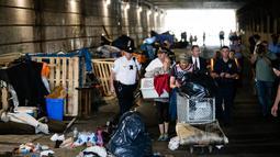 Sepasang wanita dan pria yang tinggal di bawah jembatan membawa barang mereka usai diusir petugas di Philadelphia (30/5). Para tunawisma ini diusir karena tempat mereka tinggal biasa digunakan untuk mengkonsumsi heroin. (AP Photo/Matt Rourke)