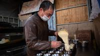 Seorang pedagang menuangkan adonan ke dalam cetakan kue di pasar di Beijing (20/11). (AFP Photo/Nicolas Asfouri)