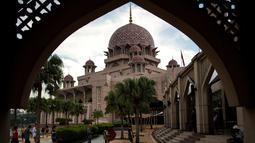 Gambar yang diambil pada 22 November 2017, menunjukkan wisatawan berjalan di sekitar Masjid Pink di kawasan Putrajaya, Malaysia. Selain warna yang unik, masjid ini juga dilengkapi dengan kubah berisikan lukisan dan kaligrafi indah. (MANAN VATSYAYANA/AFP)