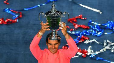 Petenis peringkat satu dunia, Rafael Nadal mengangkat trofi AS Terbuka 2017 setelah mengalahkan petenis Afrika Selatan, Kevin Anderson di New York, Minggu (10/9).Nadal mengalahkan Kevin Anderson dengan skor 3-0. (AFP PHOTO/TIMOTHY A. CLARY)