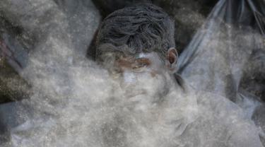 Seorang pekerja India mencampur bubuk mesiu untuk membuat petasan di sebuah pabrik di pinggiran Ahmadabad, Selasa (15/10/2019).  Menjelang Festival Diwali atau Festival Cahaya, produsen petasan di india dibanjiri pesanan. (AP Photo/Ajit Solanki)