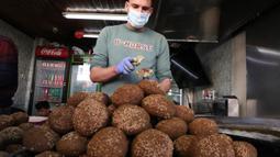 Juru masak Palestina mengenakan sarung tangan dan masker bersiap menggoreng falafel di sebuah restoran lokal di kota Hebron, Tepi Barat yang diduduki pada 29 April  2020. Pada bulan suci Ramadan, falafel sering dimakan sebagai hidangan buka puasa. (HAZEM BADER / AFP)