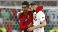Pemain Portugal Cristiano Ronaldo (kiri) dan pemain Prancis Karim Benzema (kanan) meninggalkan lapangan bersama saat turun minum pada pertandingan Grup F Euro 2020 di Puskas Arena, Budapest, Hungaria, Rabu (23/6/2021). Laga berakhir imbang 2-2. (Franck Fife, Pool photo via AP)