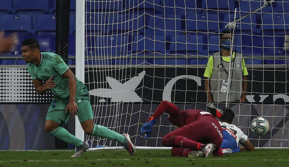 Pemain Real Madrid Casemiro (kiri) melakukan selebrasi usai mencetak gol ke gawang Espanyol pada pertandingan La Liga Spanyol di Stadion Cornella-El Prat, Barcelona, Spanyol, Minggu (28/6/2020). Real Madrid menang 1-0 dan menggeser Barcelona dari puncak klasemen. (AP Photo/Joan Monfort)