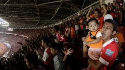 Suporter Persija Jakarta menggendong anaknya saat merayakan gelar juara Liga 1 di SUGBK, Jakarta, Minggu (09/12). Persija menang 2-1 atas Mitra Kukar. (Bola.com/M Iqbal Ichsan)