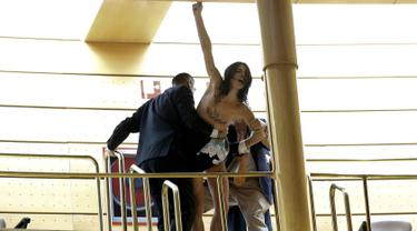 "Petugas berusaha mengamankan aktivis Femen saat sidang parlemen di Madrid, Spanyol (9/9/2015). Coretan di tubuh bertuliskan ""I decide"", menolak rencana pembatasan aborsi untuk wanita di bawah 18 tahun. (REUTERS/Andrea Comas)"