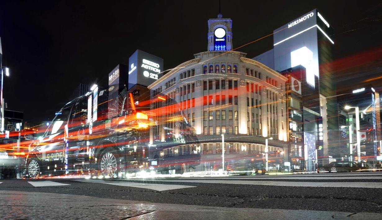 Mobil melintas di kawasan Ginza, Tokyo, Jepang, Rabu (6/1/2021). Ibu kota Jepang itu mengkonfirmasi lebih dari 1.500 kasus baru virus corona COVID-19 pada 6 Januari 2021. (AP Photo/Eugene Hoshiko)