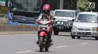 Warga mengoperasikan telepon seluler sambil mengendarai sepeda motor di Jalan Gatot Subroto, Jakarta, Kamis (8/3). Pengemudi yang membaca pesan teks pada telepon genggam akan memiliki risiko kecelakaan 23 kali lebih tinggi. (Liputan6.com/Arya Manggala)