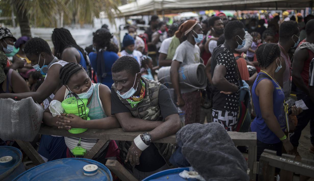 Para migran Haiti berkumpul sebelum menaiki perahu menuju Capurgana dekat perbatasan dengan Panama, di Necocli, Kolombia, Rabu (28/7/2021). Ribuan migran telah berkumpul di Necocli saat mereka bergerak ke utara menuju Panama dalam perjalanan mereka ke perbatasan AS. (AP Photo/Ivan Valencia)