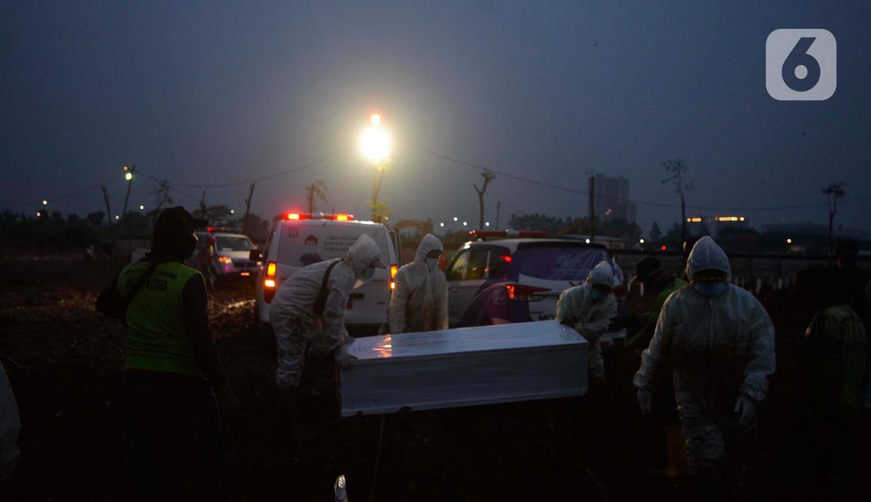 Petugas memakamkan jenazah korban Covid-19 di TPU Rorotan Cilincing, Jakarta, Sabtu (19/6/2021). Pemakaman jenazah dengan protokol covid-19 terus meningkatdalam satu pekan terakhir, seiring dengan lonjakan kasus corona di Ibu kota. (merdeka.com/Imam Buhori)