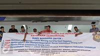 Petugas memasang spanduk sosialisasi peningkatan kesadaran untuk menghormati hasil karya intelektual di salah satu pusat perbelanjaan elektronik di Mangga Dua, Jakarta, Rabu (18/5).(Liputan6.com/Immanuel Antonius)
