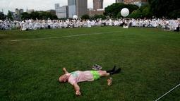 Seorang pria berbaring di rumput dengan latar belakang Diner en blanc di Rockefeller Park, New York, Rabu (17/7/2019). New York City Diner en Blanc adalah sebuah pesta makan malam rahasia dengan pakaian bernuansa putih yang diadopsi dari budaya Prancis. (TIMOTHY A. CLARY / AFP)