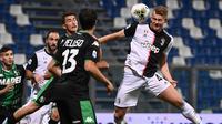 Bek Juventus,  Matthijs de Ligt menyundul bola ke arah gawang Sassuolo pada pertandingan lanjutan Liga Serie A Italia di stadion Mapei di Reggio Emilia (15/7/2020). Juventus bermain imbang 3-3 atas Sassuolo. (AFP/Marco Bertorello)
