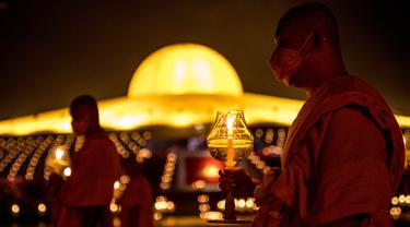 Biksu Buddha memegang lilin selama perayaan Makha Bucha di tengah pandemi COVID-19, di Wat Dhammakaya, utara Bangkok, Jumat (26/2/2021). Upacara keagamaan ini pun menjadi salah satu yang terbesar di Thailand karena banyaknya umat Buddha yang tinggal di wilayah Gajah Putih. (Jack TAYLOR/AFP)