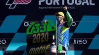Pembalap Italtrans Racing Team, Enea Bastianini, merayakan keberhasilan menyabet gelar juara dunia Moto2 2020 di Sirkuit Portemao Portugal, Minggu (22/11/2020). (PATRICIA DE MELO MOREIRA / AFP)