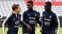 Pemain Prancis, Antoine Griezmann, Samuel Umtiti dan Benjamin Mendy berbincang saat melakukan sesi latihan jelang laga UEFA Nations League di Munich, Jerman, Rabu (5/9/2018). Prancis akan berhadapan dengan Jerman. (AFP/Franck Fife)