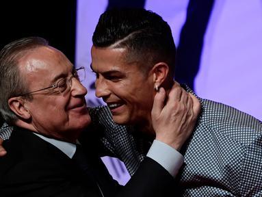 Penyerang Juventus, Cristiano Ronaldo memeluk presiden Real Madrid, Florentino Perez  usai mandapat ucapan selamat setelah meraih penghargaan media olahraga top Spanyol, Marca di Reina Victoria Theater, Madrid (29/7/2019). (AFP Photo/Javier Soriano)