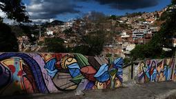 Warna-warni mural menghiasi tembok di permukiman kumuh Petare di Caracas pada 29 Mei 2019. Petare yang merupakan kawasan kumuh terbesar di Venezuela menjadi rumah bagi lebih dari 500.000 jiwa. (Photo by MARVIN RECINOS / AFP)