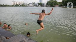 Seorang anak melompat di Danau Sunter, Jakarta, Selasa (2/2/2021). Minimnya lahan bermain anak membuat mereka memanfaatkan tempat yang tidak semestinya untuk bermain karena adanya risiko hanyut dan tenggelam bila tidak mampu untuk berenang. (Liputan6.com/Faizal Fanani)