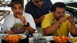 Dua orang peserta mencoba menyelesaikan makan cabai Habanero dalam Habanero Eating Contest di Restoran Chichen Itza, Los Angeles, Minggu (21/6). Dalam lomba ini setiap peserta diberikan 60 cabai Habanero dengan waktu 20 menit. (AFP PHOTO/Mark RALSTON)