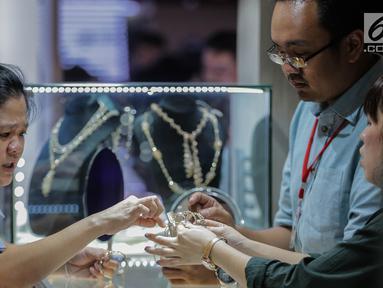 Pengunjung melihat perhiasan di salah satu stan pameran Jakarta Inernational Jewellery Fair 2019 di Jakarta, Kamis (4/4). Ajang Jakarta International Jewellery Fair 2019 diselenggarakan oleh Asosiasi Perhiasan Emas dan Permata Indonesia (APEPI) 4-7 April 2019 di JCC. (Liputan6.com/Faizal Fanani)